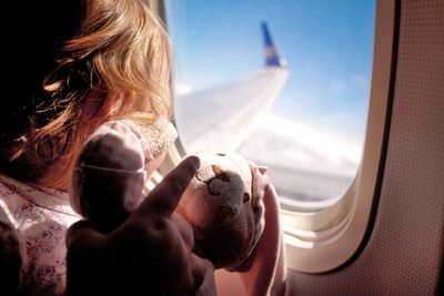 Little girl on aeroplane with teddy