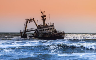 Pink sunset skies and ship wreck at Namibia coast