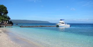 White sand beach with turquoise water and jetty with speedboat