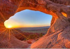 Sun rising through an arch
