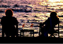 A couple looking out at the Ocean at sunset in Mahale