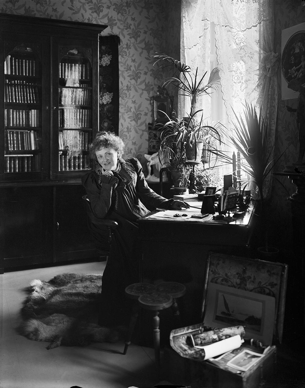 Alfhild Agrell tittar in i kameran, sittandes vid sitt skrivbord
