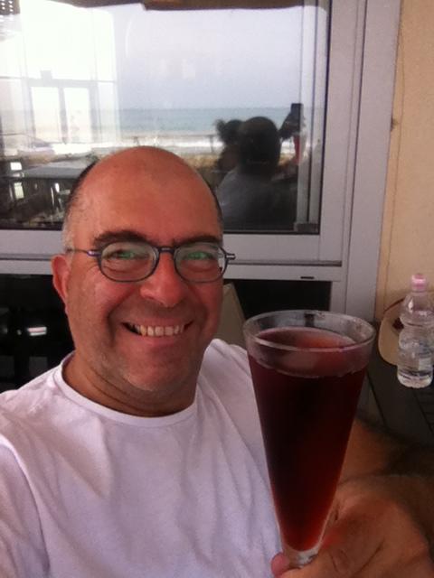 Mel Rosenberg having a drink at the beach