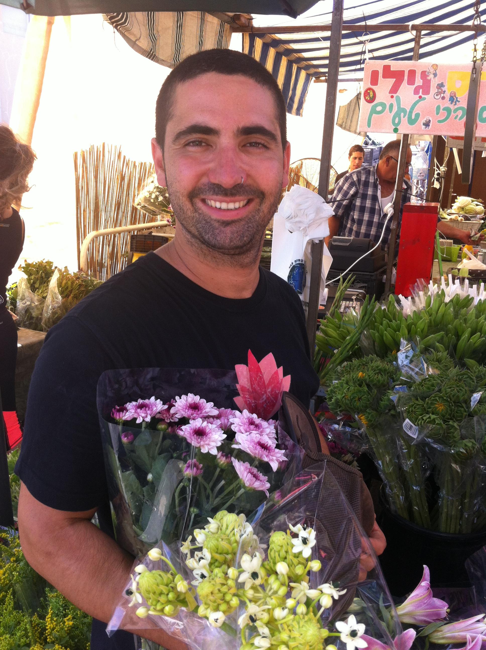 תום מוכר פרחים בשוק האיכרים בתל אביב