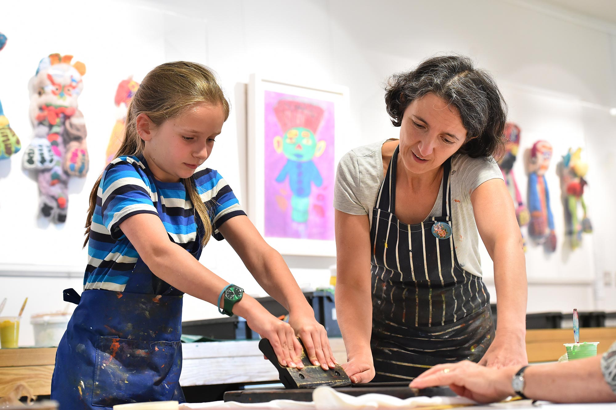 A young girl screen printing while an adult artist educator watches on.