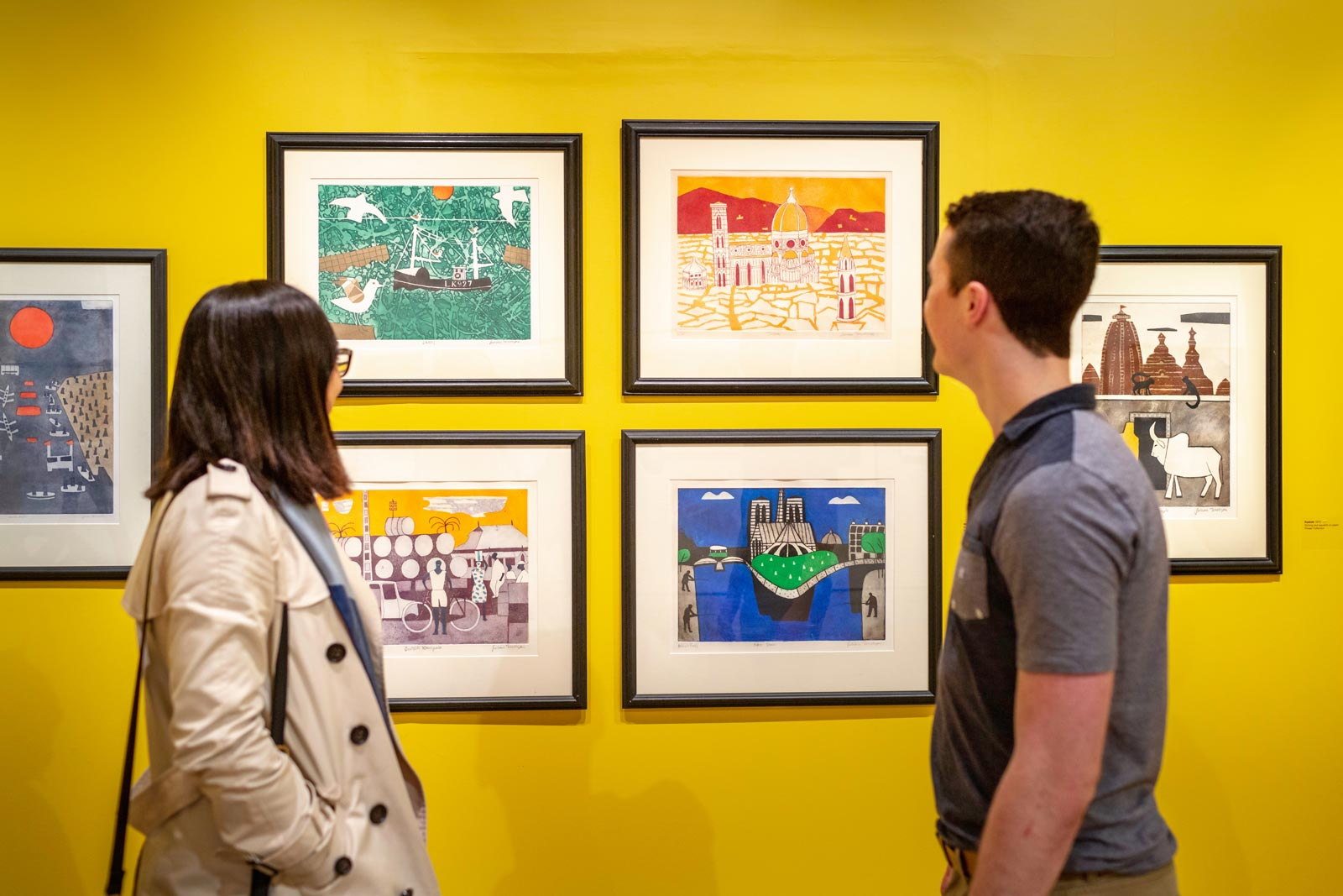 A couple stand looking at a selection of artworks hanging against a yellow wall.