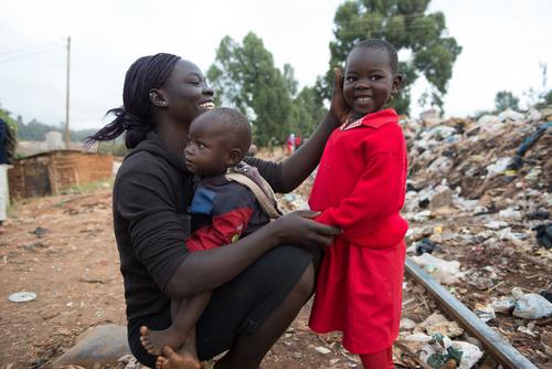 Kuvan Caroline asuu Kiberan slummissa Kenian pääkaupungin kupeessa. Hän on kahden tyttären äiti. Timclaire on 4-vuotias ja kuvassa on mukana hänen toinen tyttärensä Beatrice. Kesäkuussa vuonna 2013 Kenian terveysministeriö lanseerasi ilmaisen terveydenhuollon kaikille synnyttäville äideille. Kiberassa terveyspalvelujen saanti on kuitenkin huono. Eri kansalaisjärjestöt, Pelastakaa Lapset heidän joukossaan, paikkaavat tätä puutetta tarjoamalla neuvolapalveluja, rokotuksia ja muuta terveydenhuoltoa. Kuva: Hannah Maule-Ffinch/Pelastakaa Lapset