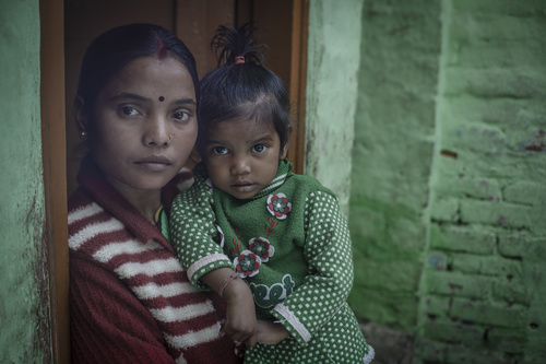 Kuvan Sunaina, 28, elää Jahangirpurin slummialueella Pohjois-Delhissä. Sunainalla ja hänen aviomiehellään on kaksi lasta, Mohit-poika, joka on iältään kuusi vuotta ja tytär Suriti, joka on kaksi vuotta. Koko perhe asuu yhdessä huoneessa. Sunainalla on monia huonoja kokemuksia käynneistä paikallisessa julkisessa sairaalassa. Kuva: CJ Clarke/Pelastakaa Lapset