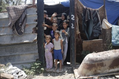 A family waves goodbye from temporary accommodation on the site of their former home, Beit Hanoun. Photo: Kuva: Anas Baba/Save the Children