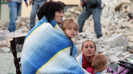 TOPSHOT - Victims sit among the rubble of a house after a strong earthquake hit Amatrice on August 24, 2016. Central Italy was struck by a powerful, 6.2-magnitude earthquake in the early hours, which has killed at least three people and devastated dozens of mountain villages. Numerous buildings had collapsed in communities close to the epicenter of the quake near the town of Norcia in the region of Umbria, witnesses told Italian media, with an increase in the death toll highly likely. / AFP / FILIPPO MONTEFORTE        (Photo credit should read FILIPPO MONTEFORTE/AFP/Getty Images)