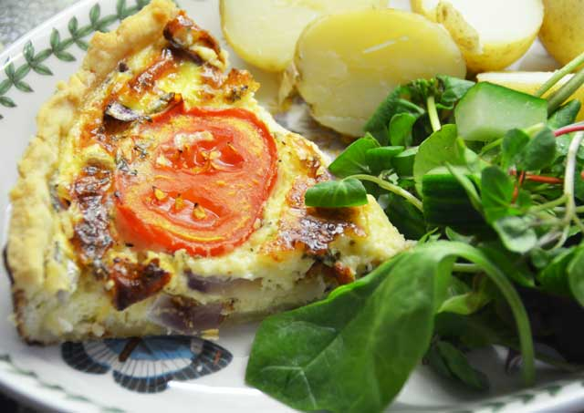 quiche - one slice served with salad and new potatoes