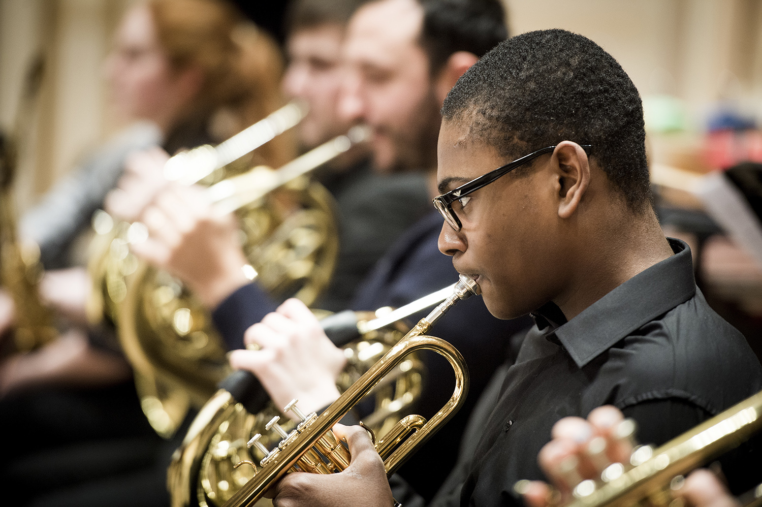 Young French horn player performing
