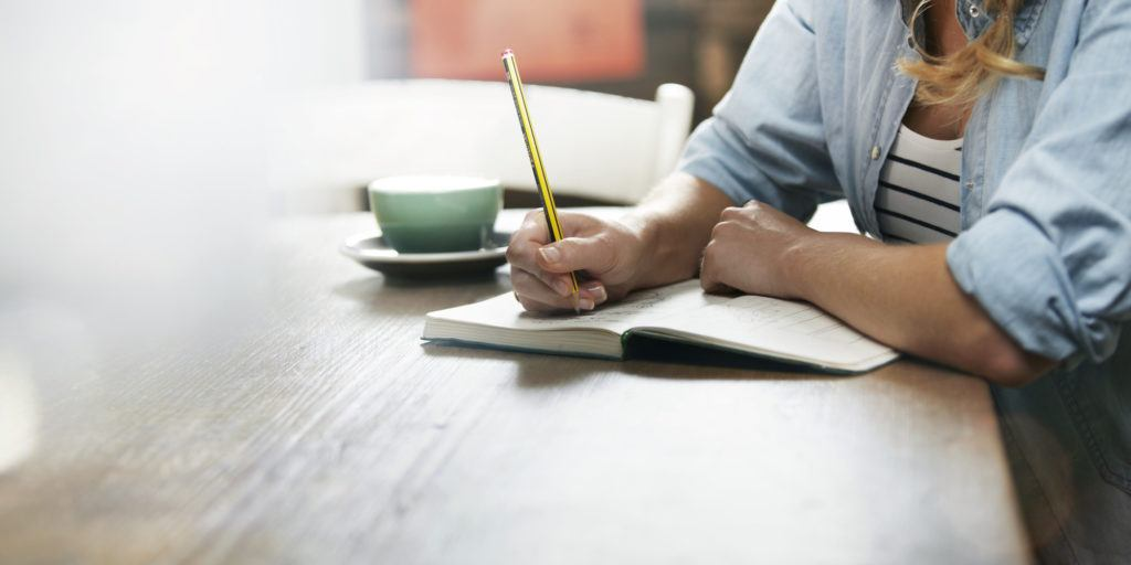 Woman writing in her notebook. Cup of coffee on her desk