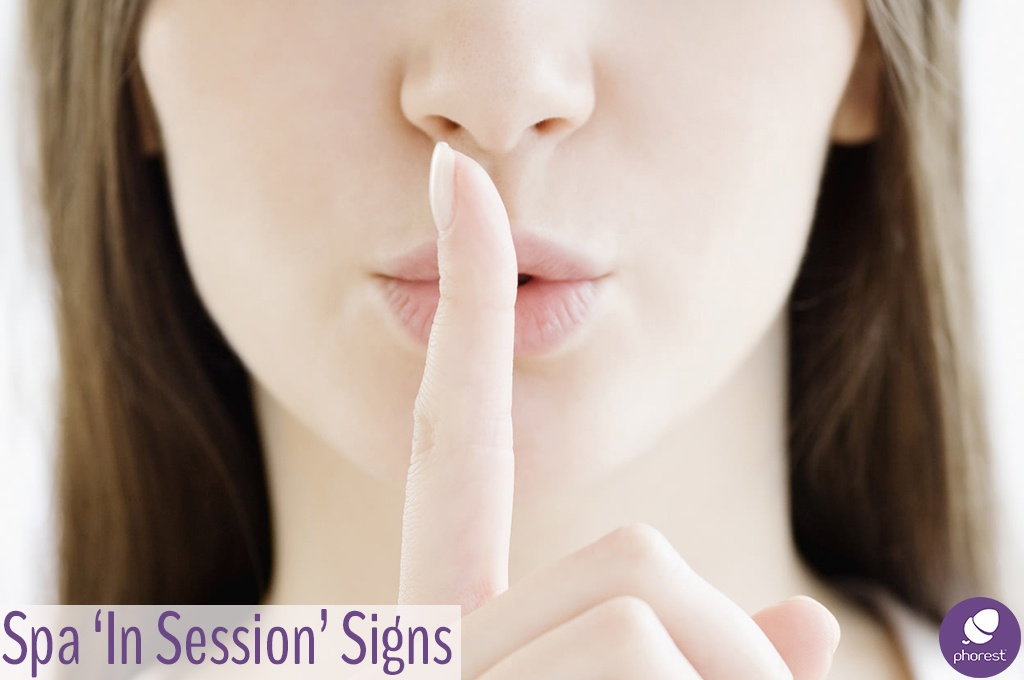 woman holding her finger to her mouth in a shush gesture. Salon and Spa in session sign