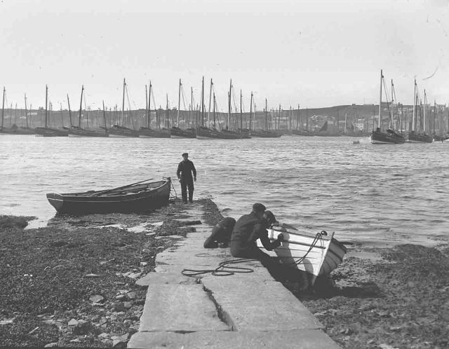 Men painting boat on one of the Holms