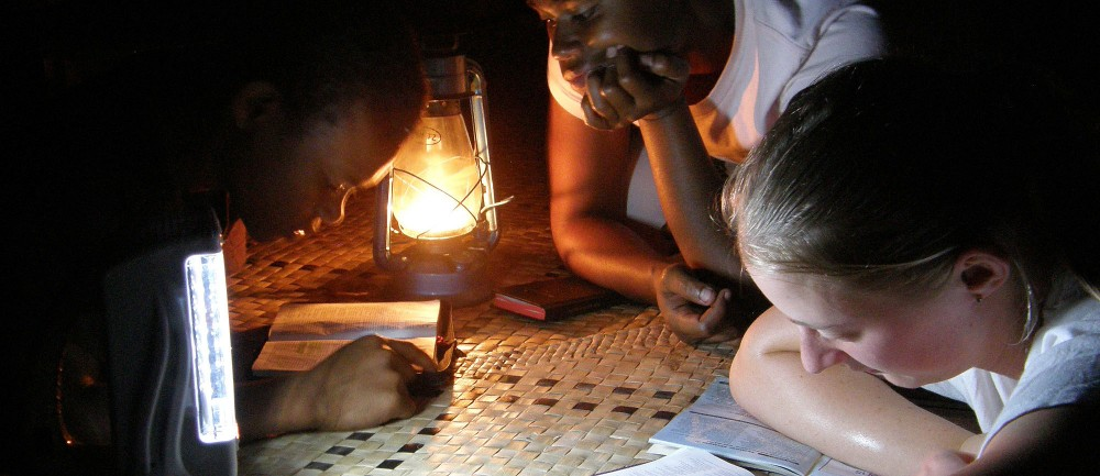 Heather Penman (right) shares a Bible reading by lamp light with children from Vanuoso Village, Gau Island, Fiji. She was one of two young women sent by the Bible Society in New Zealand to join a Dayspring Ministries team which travelled on the yacht ÂSeahawk to deliver Bibles to remote Fijian islands in September 2010. (project 86421)