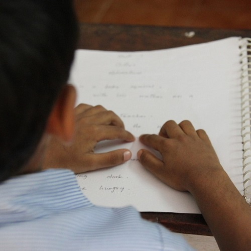 kuvassa pistekirjoitusta lukeva lapsi