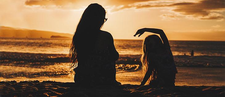 Äiti ja lapsi ilta-auringossa rannalla