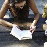 Nuoret istuvat koulukirjojen kanssa pöydän äärellä