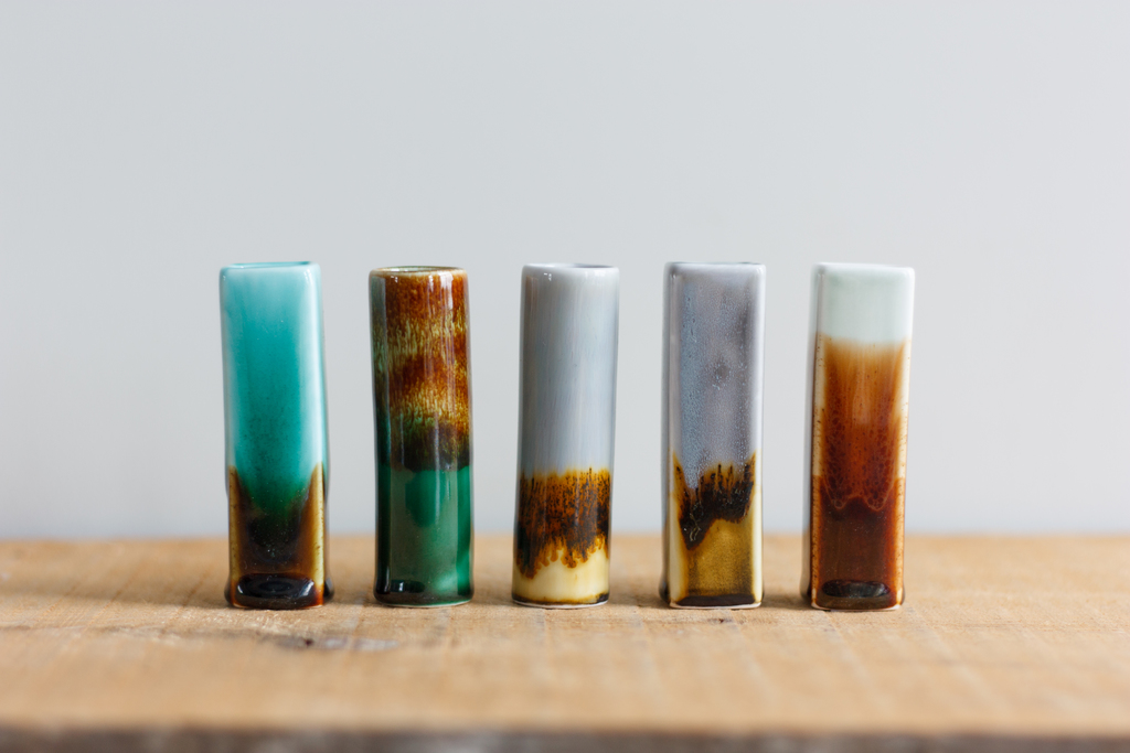 Line up of glazed daisy vases