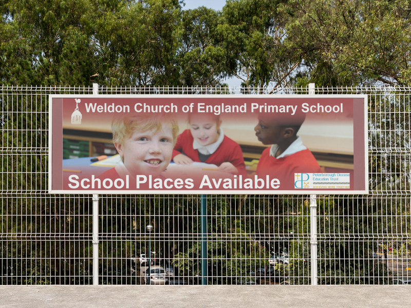 horizontal-banner-mockup-hanging-from-a-fence-at-a-school-a10572.png