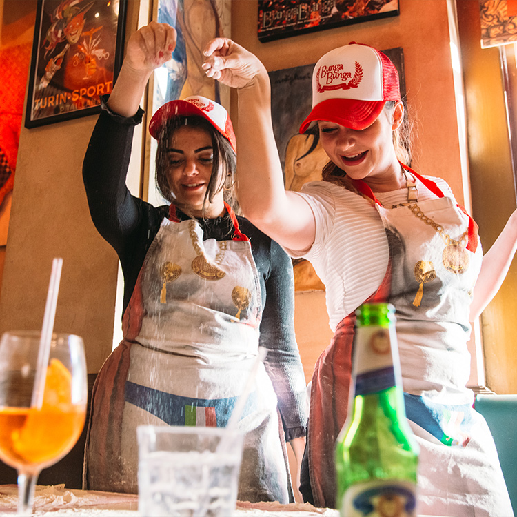 Photograph: Two girls sprinkling flour on pizza dough
