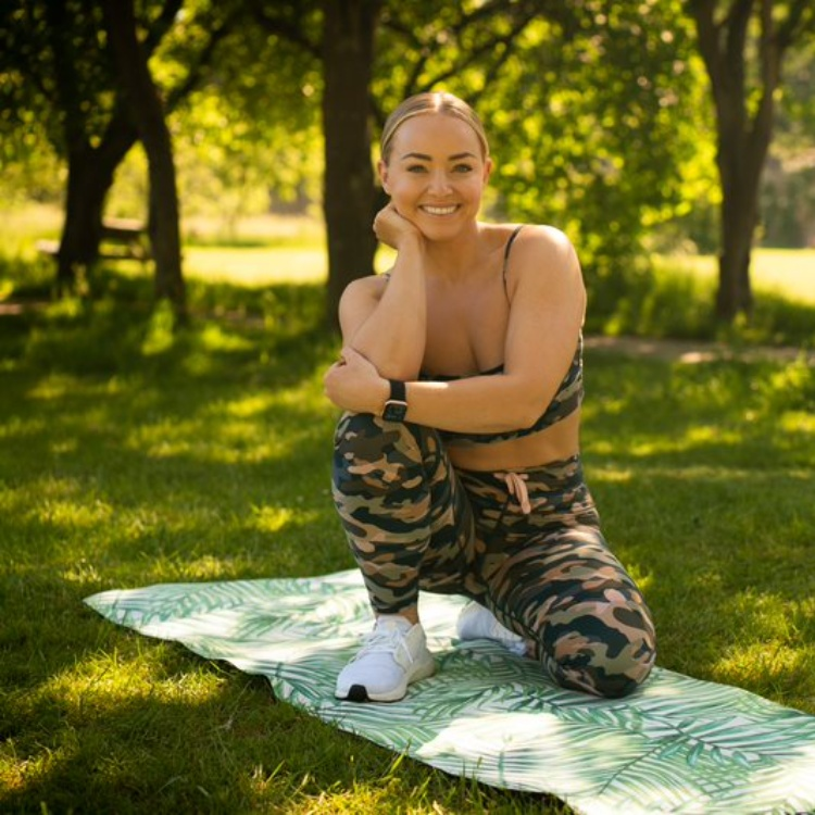 Photograph: Alice Liveing on a yoga mat outdoors