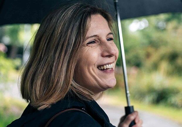 Woman smiling holding an umbrella