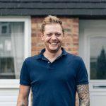 Andrew smiling at front door