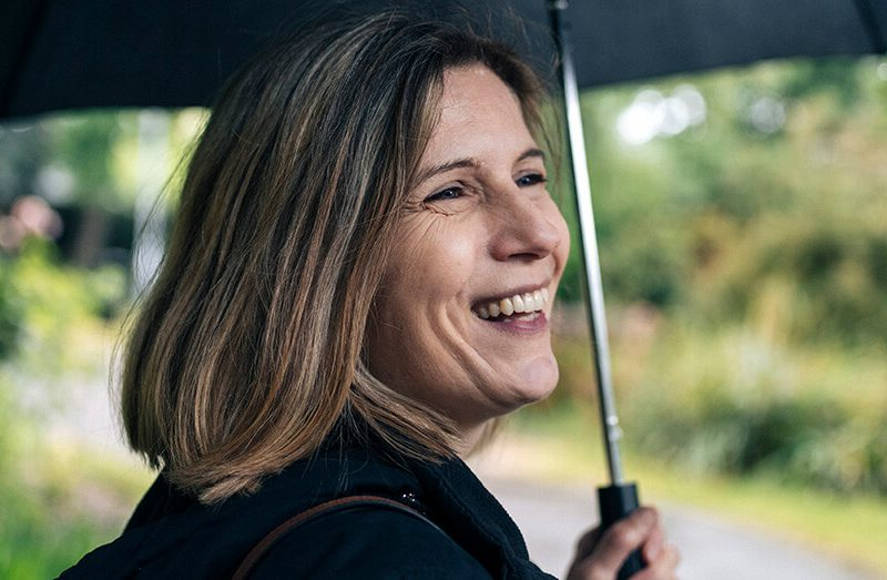 Lady smiling while holding an umbrella