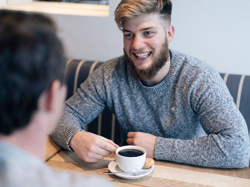 Ben smiling in a cafe with coffee