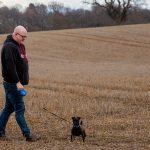 Martin walking dog in field