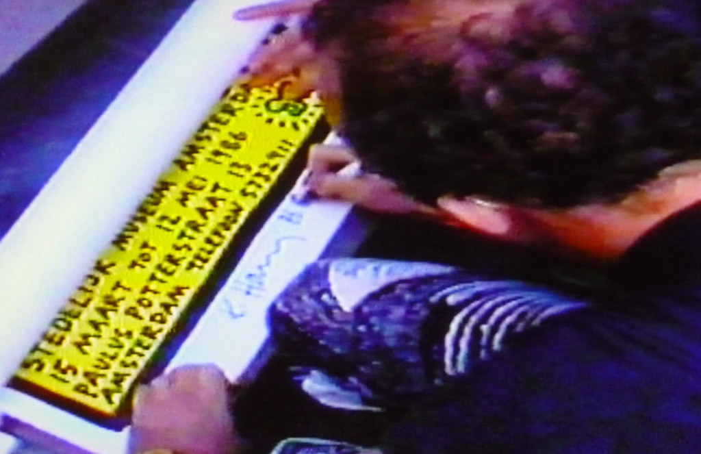 Keith Haring signing a poster after his lecture and tv-interview, Stedelijk Museum, Amsterdam, 15 March 1986; local TV Photo still: Chris Reinewald.