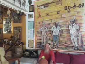 Portret Stanley Brown in zijn woning voor een werk van kunstenaar Jean Girigori met daarop leiders van de 30 mei-opstand: vanaf links Stanley, Papa Godett en Amadornita. Foto: Stephanie Archangel.