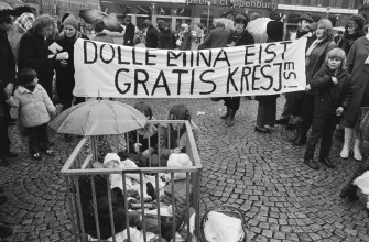 "Dolle Mina (""Crazy Mina"") members celebrate their first anniversary, Amsterdam; demonstration for free ""kresjes"" (childcare) on the Dam; children in playpen, 30 January 1971. Photo collection Anefo/Nationaal Archief"
