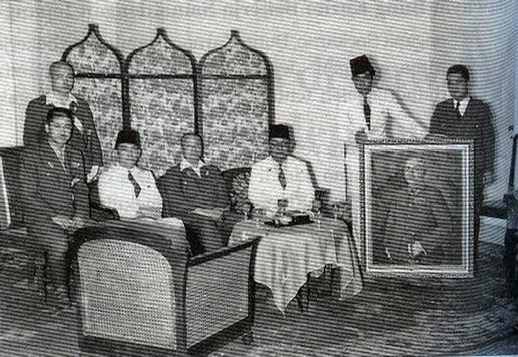 Meeting with Japanese officials, including General Imamura (seated, center), with Sukarno in Jakarta. The painter Basoeki Abdullah is holding the painting being presented, Portrait of General Imamura, 1942. Source: Aiko Kurusawa