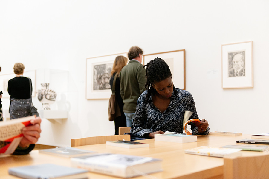 Visitors to the exhibition at the reading table with publications by Aimé Césaire, Albert Memmi, David Diop, Fouad Laroui, Frederick Brown and Jan and Leo Lucassen, among others. Photo: LNDW Studio.