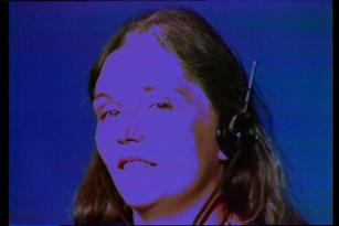 Het hoofd van een witte vrouw met middellang haar en koptelefoon tegen een blauwe achtergrond.
