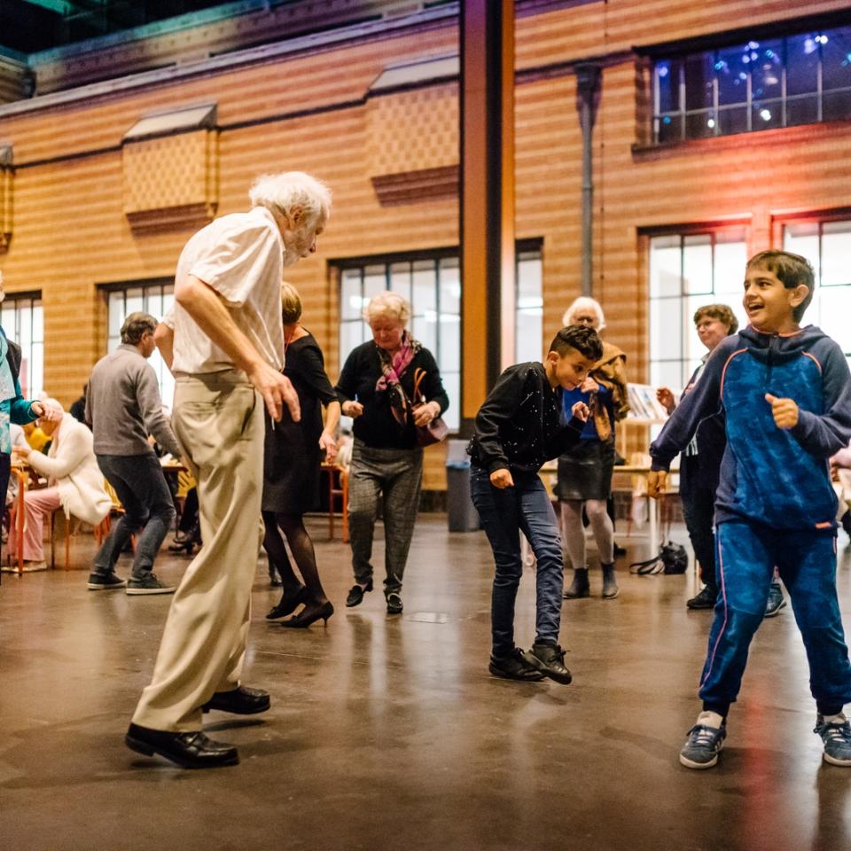 Kinderen, ouderen en volwassenen dansen in het Gemeentemuseum Den Haag