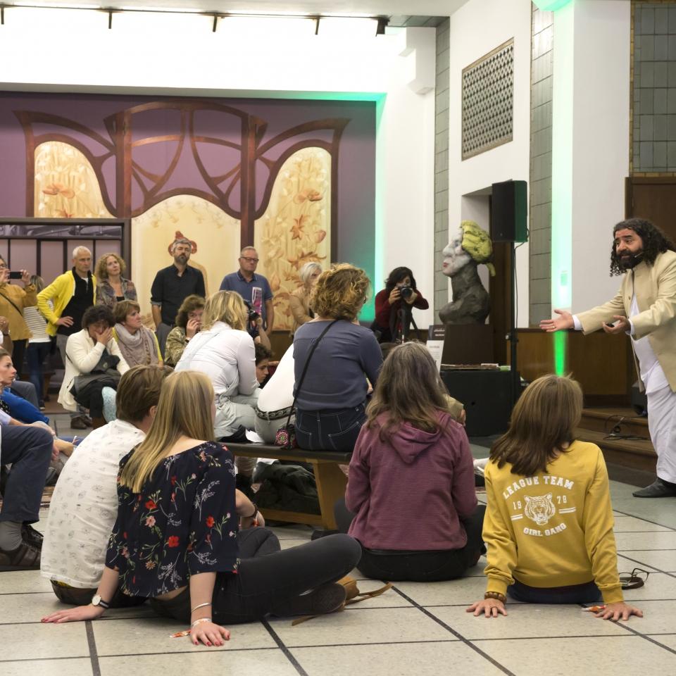 Man vertelt verhaal in het museum aan een groep bezoekers tijdens de museumnacht in het Gemeentemuseum Den Haag
