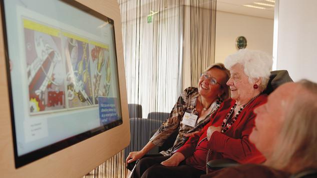 Twee ouderen gebruiken de Museumtafel bij hen in de zorginstelling.