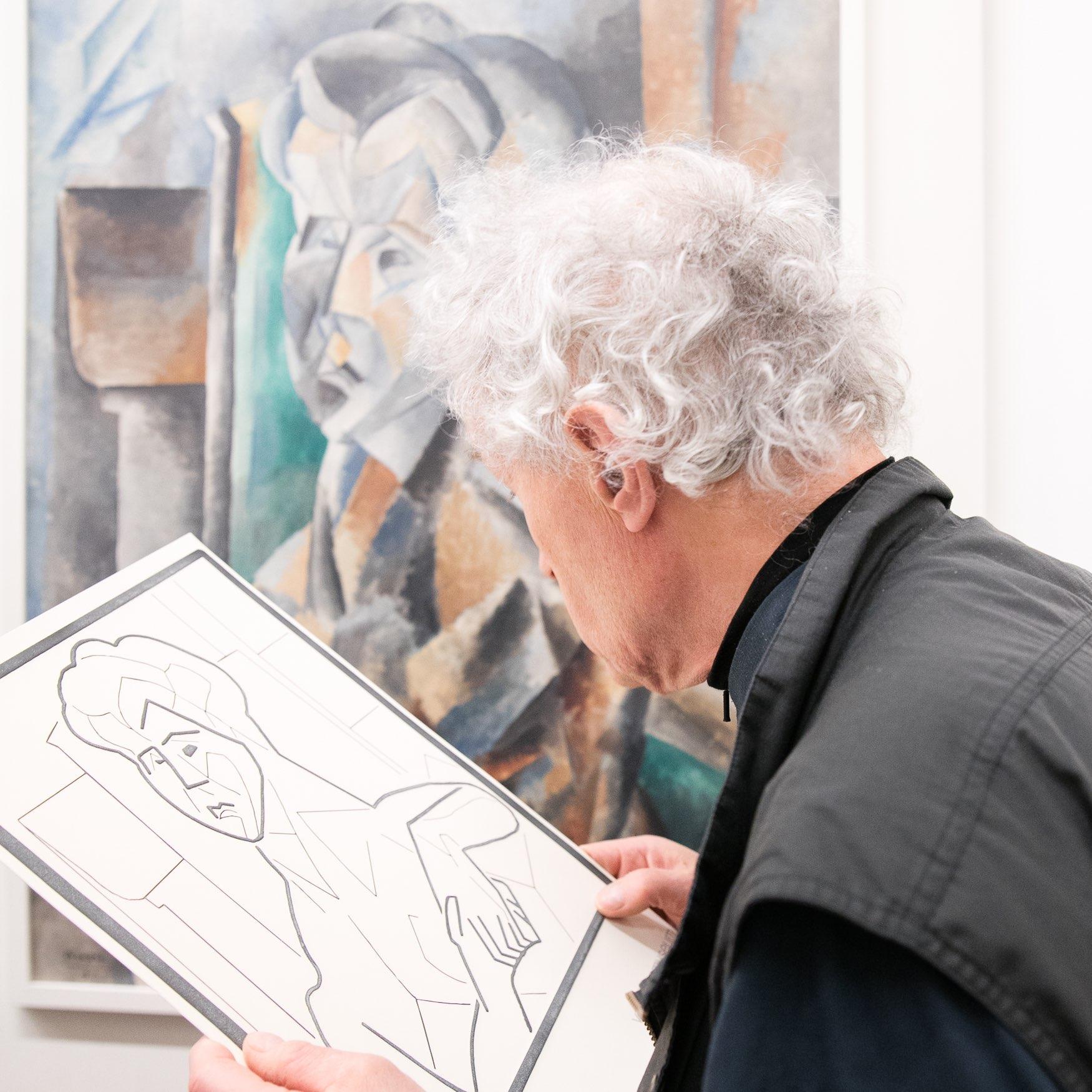 Slechtziende bezoeker betast een reproductie in de vorm van een reliëftekening van een schilderij.