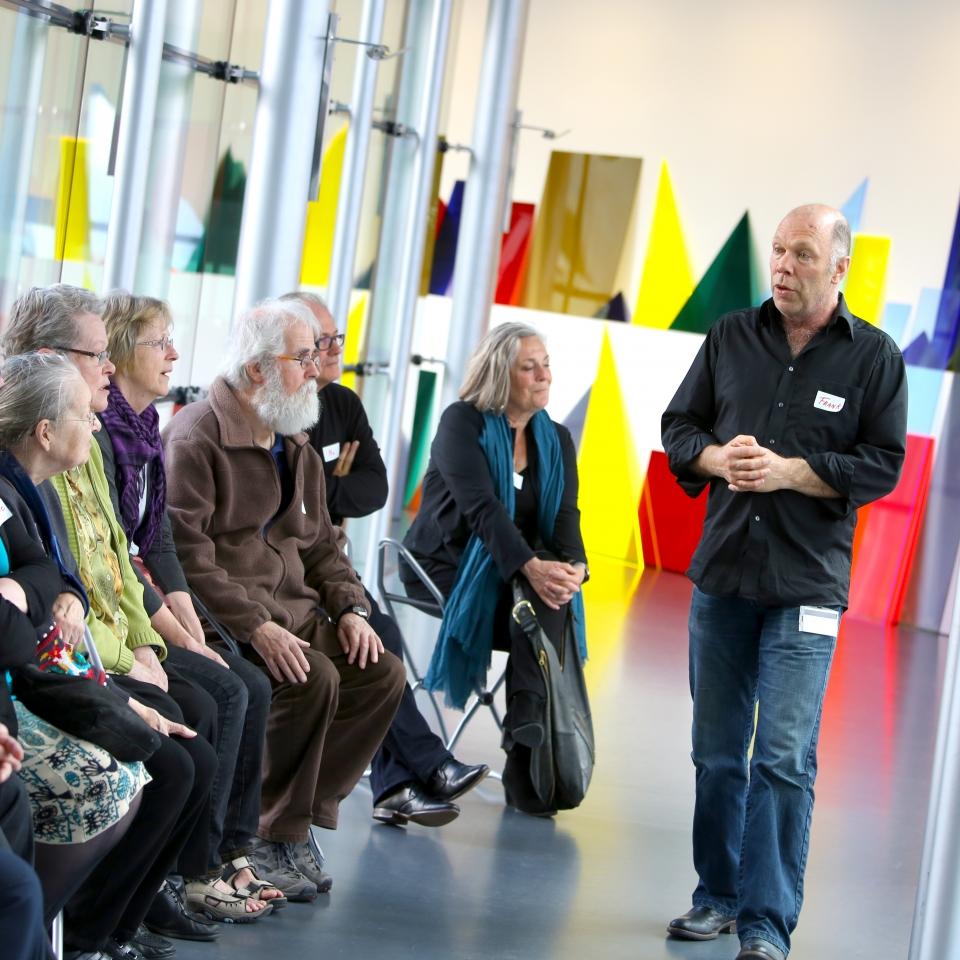 Foto van een rondleider van Onbeperkt Van Abbe die een tour geeft aan mensen met dementie. Zij zitten op klapstoeltjes op zaal. Op de achtergrond zijn vaag geometrische figuren zichtbaar die een kunstwerk vormen. De rondleider loopt voor de bezoekers langs die allemaal naar hem kijken.