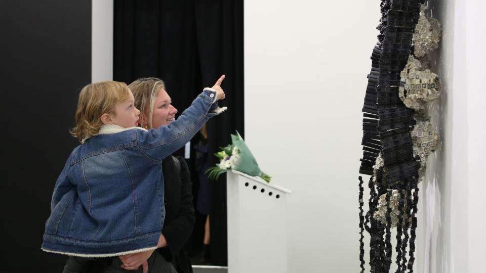 Twee bezoekers wijzen naar tentoongestelde objecten in de tentoonstelling van NEST