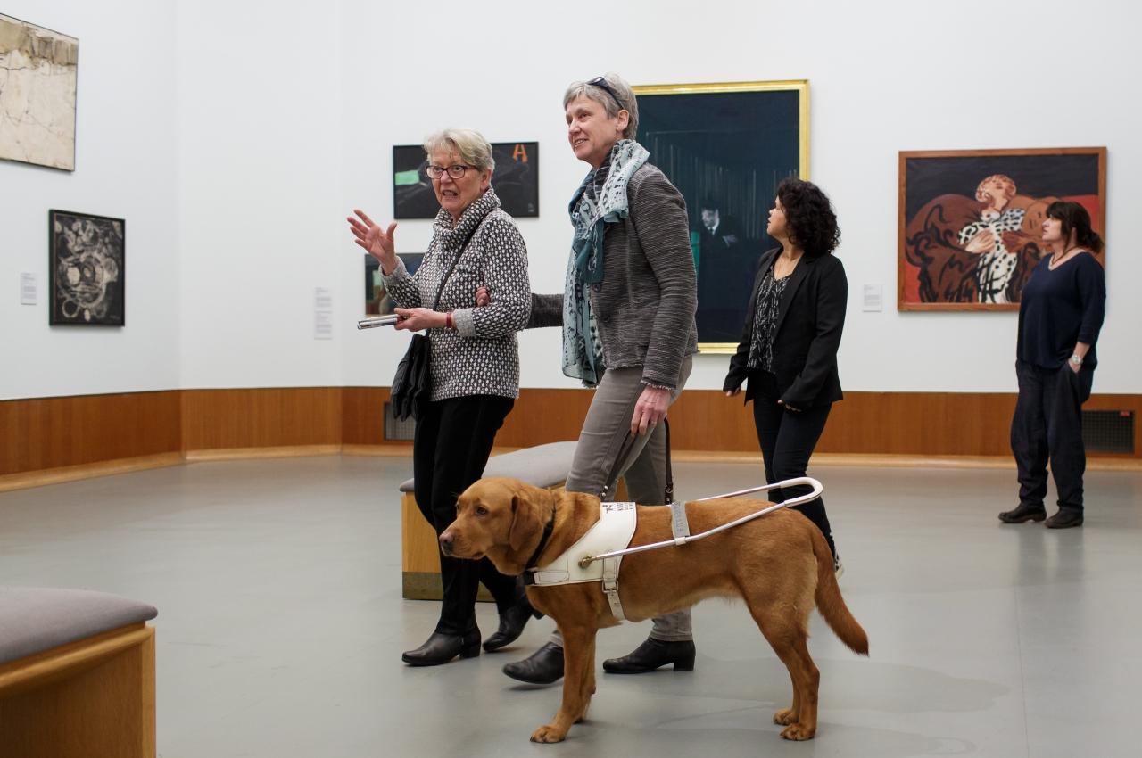 Vrouw met blindengeleidehond krijgt uitleg bij een schilderij in het museum Boijmans-van Beuningen