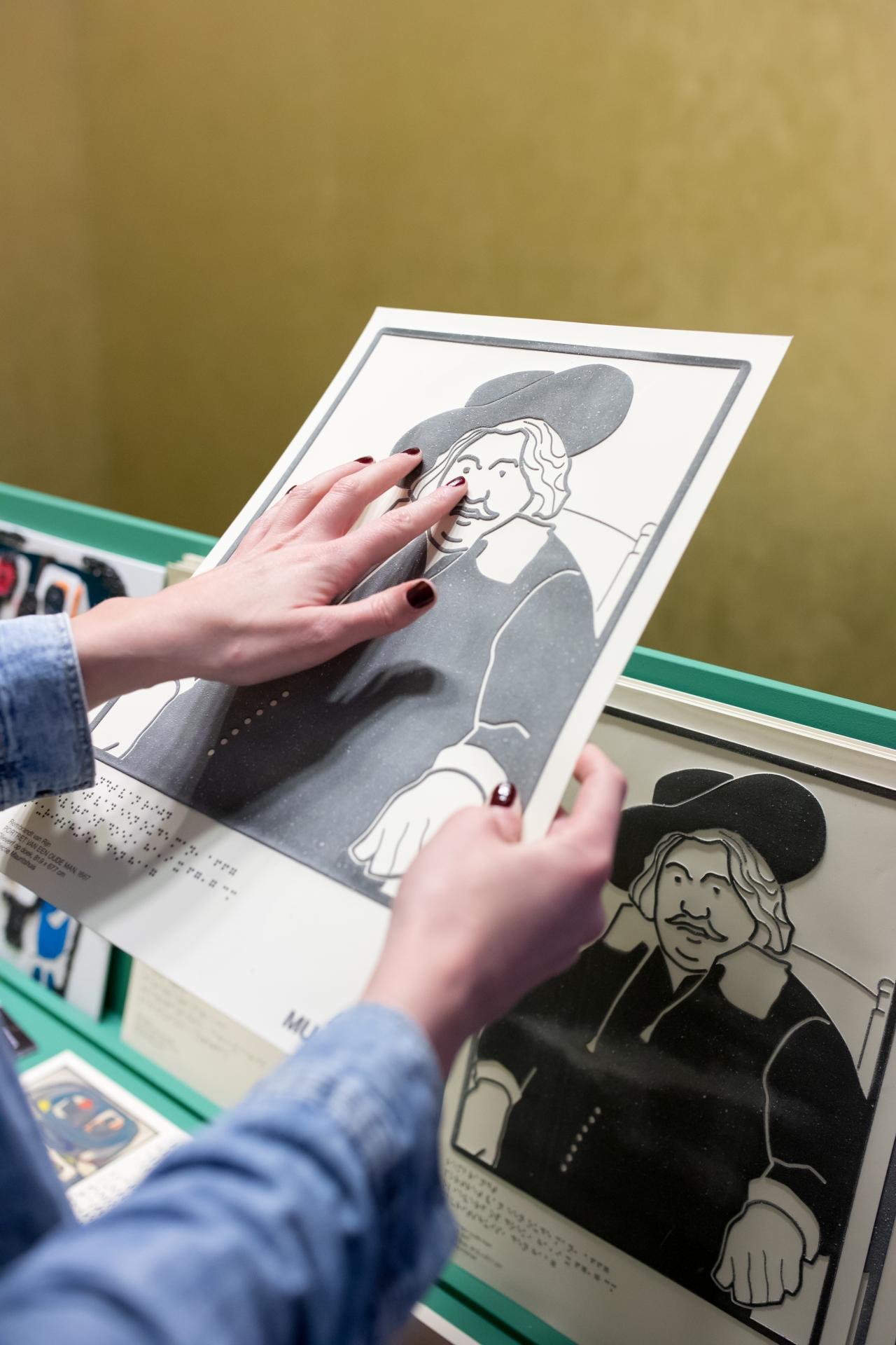 Bezoeker bekijkt kunstwerk met behulp van een voelplaat