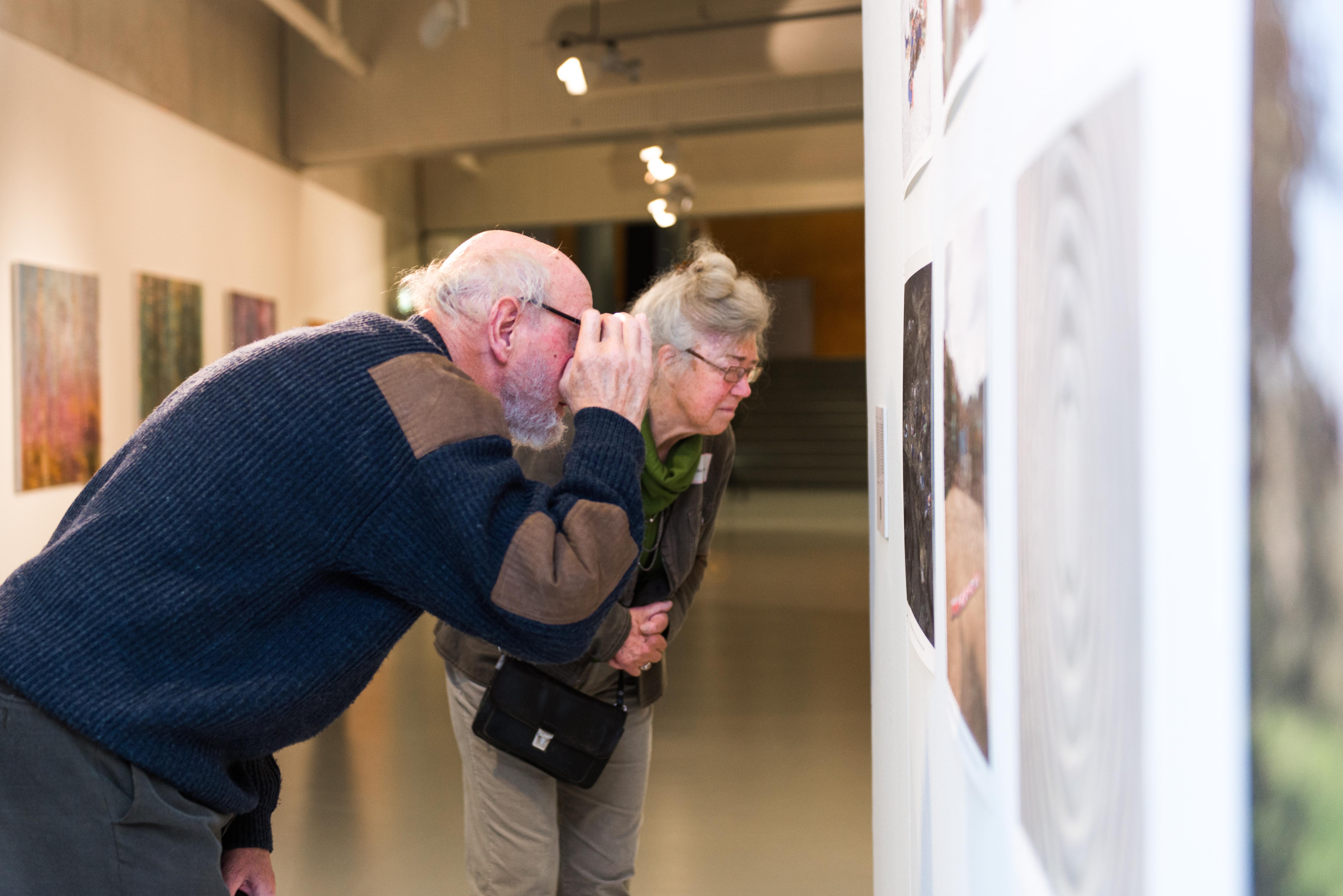 Twee bezoekers bekijken een kunstwerk van dichtbij