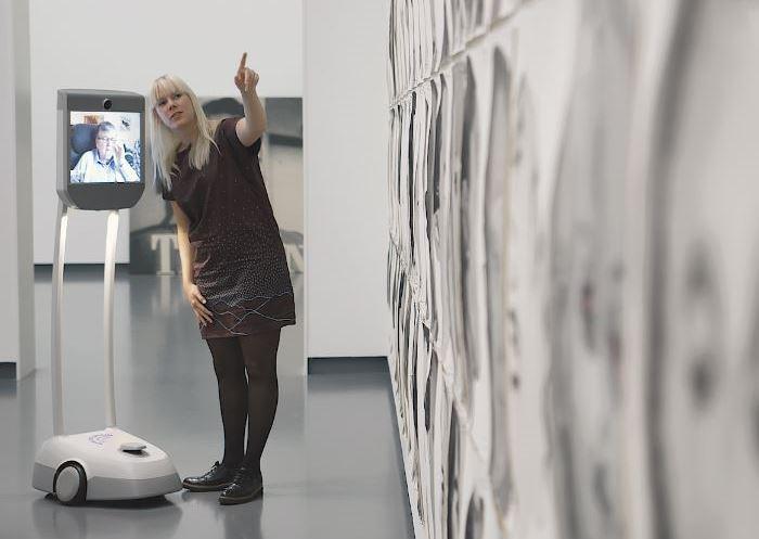 Marleen Hartjes leidt een bezoeker via de museumrobot rond