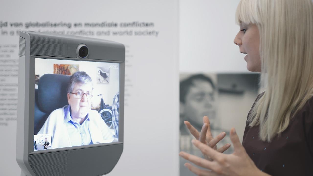 Marleen Hartjes leidt bezoeker rond via de museumrobot