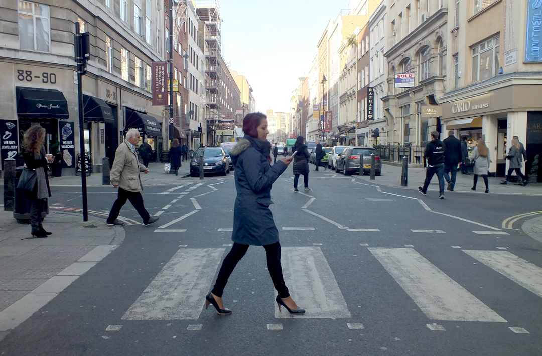 A person on a zebra crossing, looking at their phone